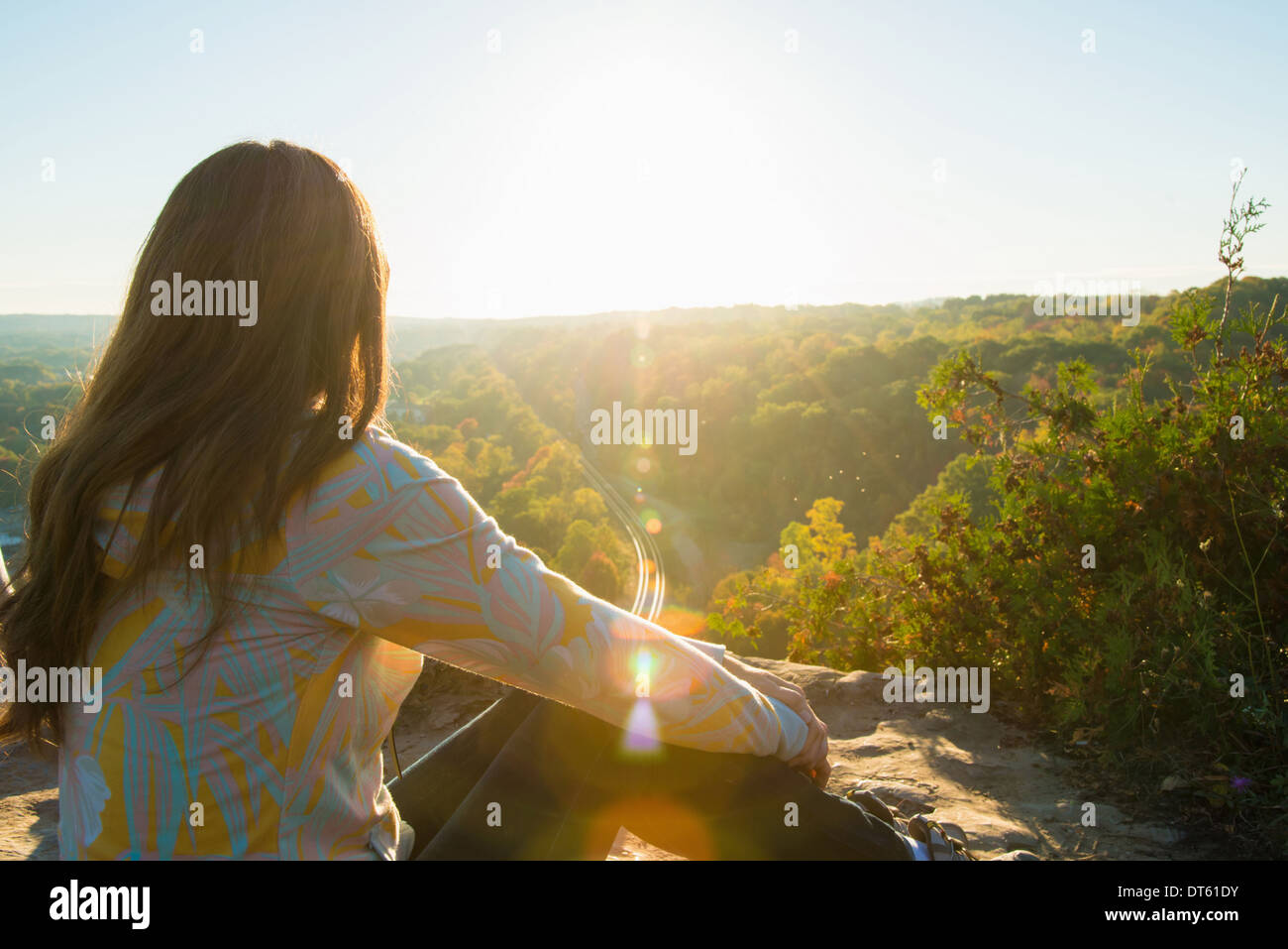 Mid adult woman sitting on elevated rock watching sunrise - Stock Image