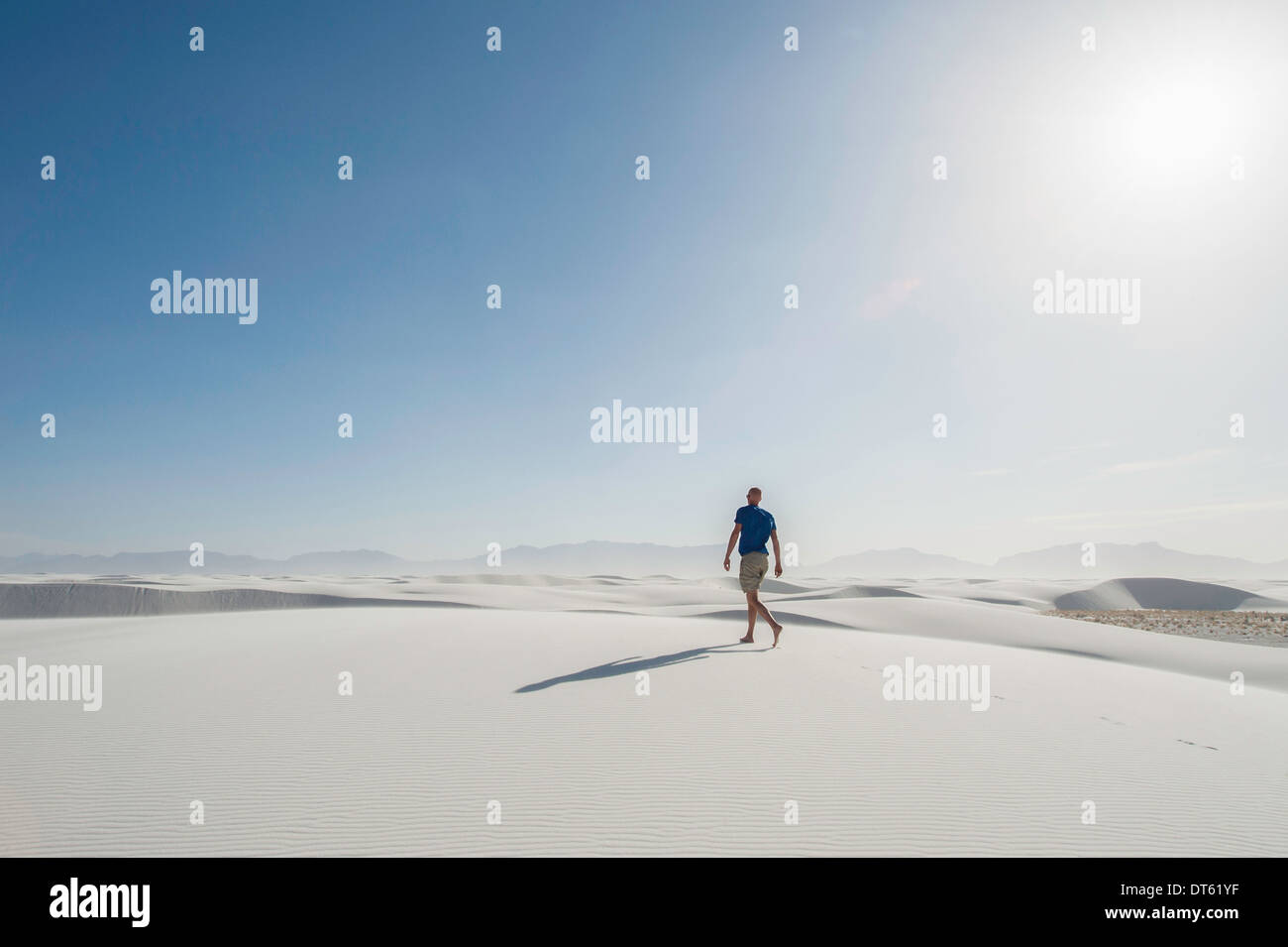 Young man walking on sand dune, White sands, New Mexico, USA - Stock Image