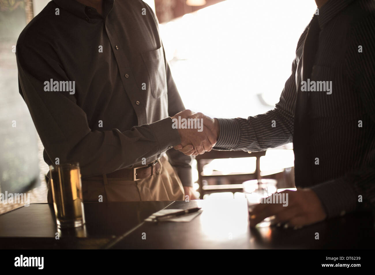 Two businessmen shaking hands in wine bar - Stock Image