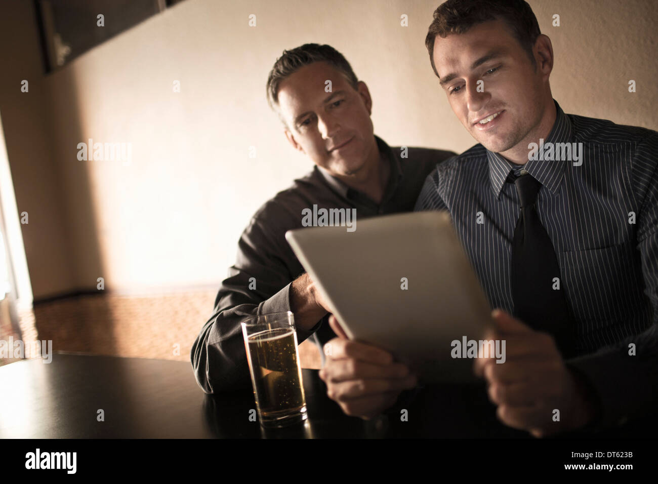 Two business colleagues looking at digital tablet in wine bar - Stock Image