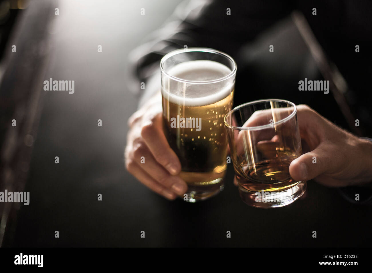 Close up of two men toasting drinks in bar - Stock Image