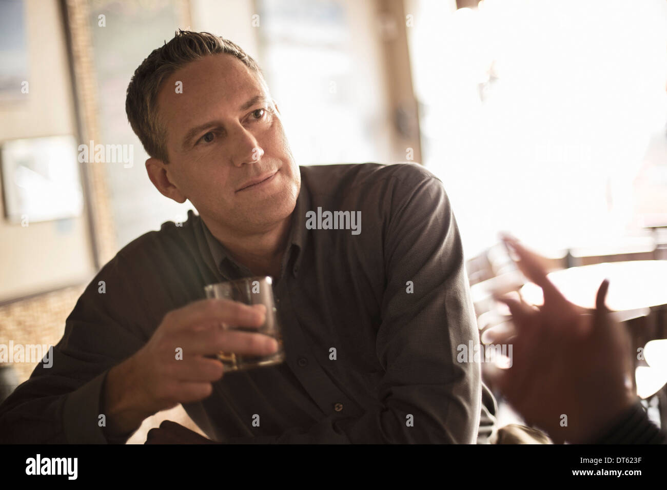 Two businessmen chatting in wine bar - Stock Image
