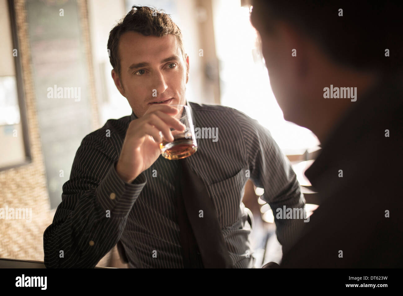 Two businessmen having a drink in wine bar - Stock Image