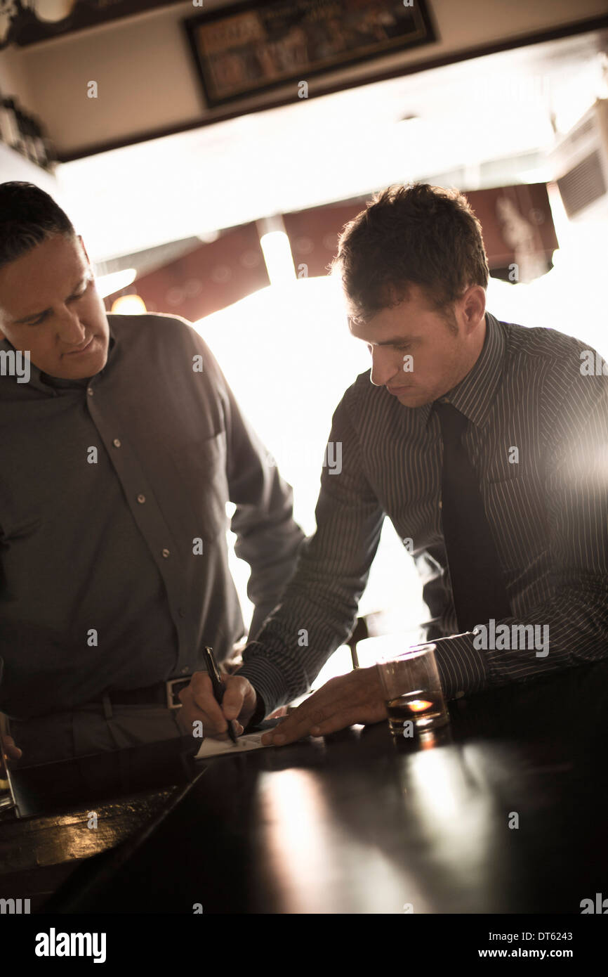 Two businessmen signing contract in wine bar - Stock Image