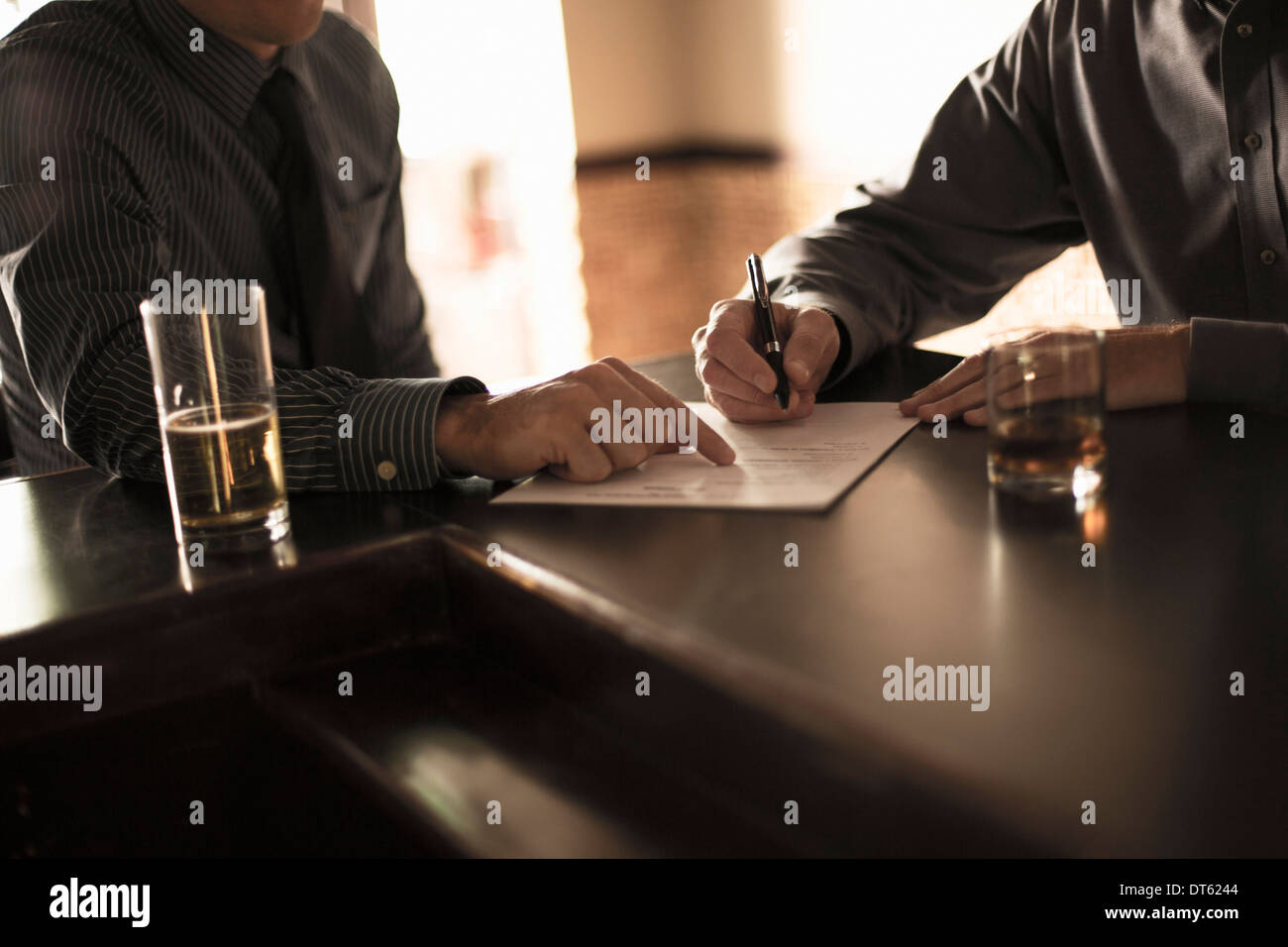 Partners signing business contract in a bar - Stock Image