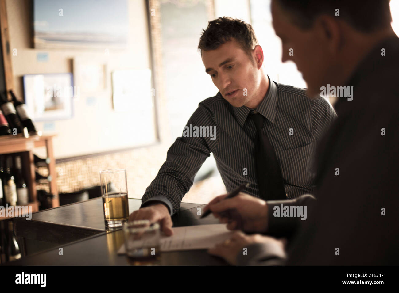 Partners signing business contract in a wine bar - Stock Image