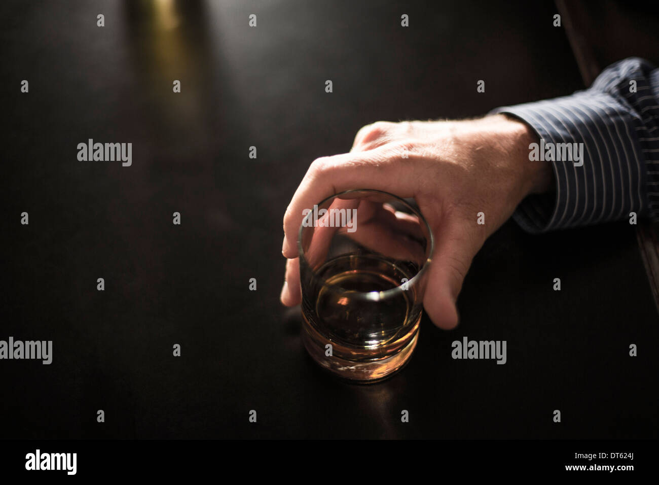 Close up of solitary man with drink in bar - Stock Image