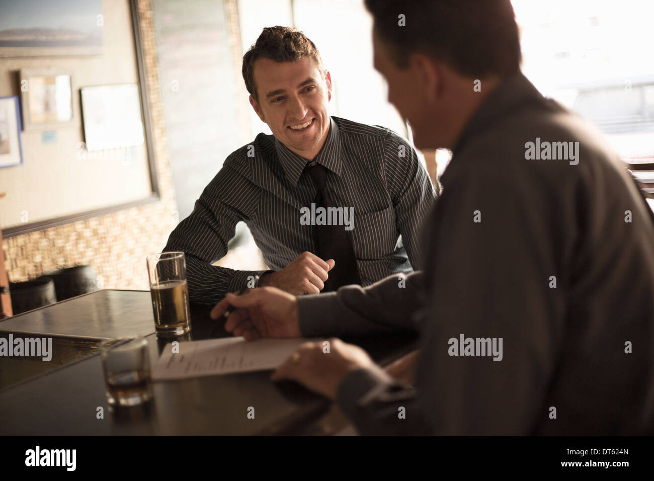 Business partners signing contract in a wine bar - Stock Image