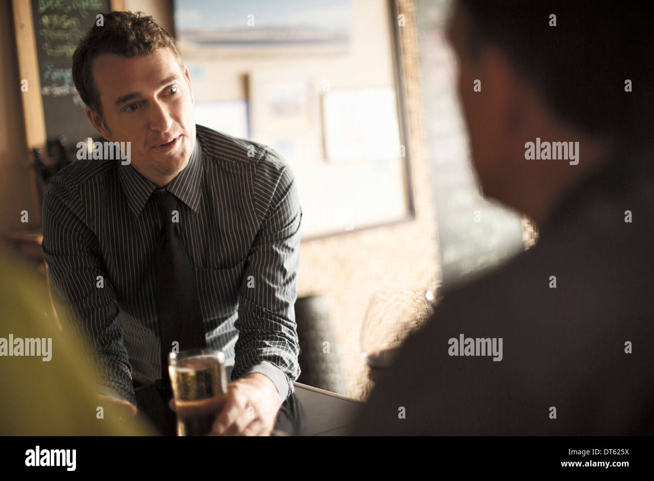 Business colleagues enjoying a drink in a wine bar - Stock Image