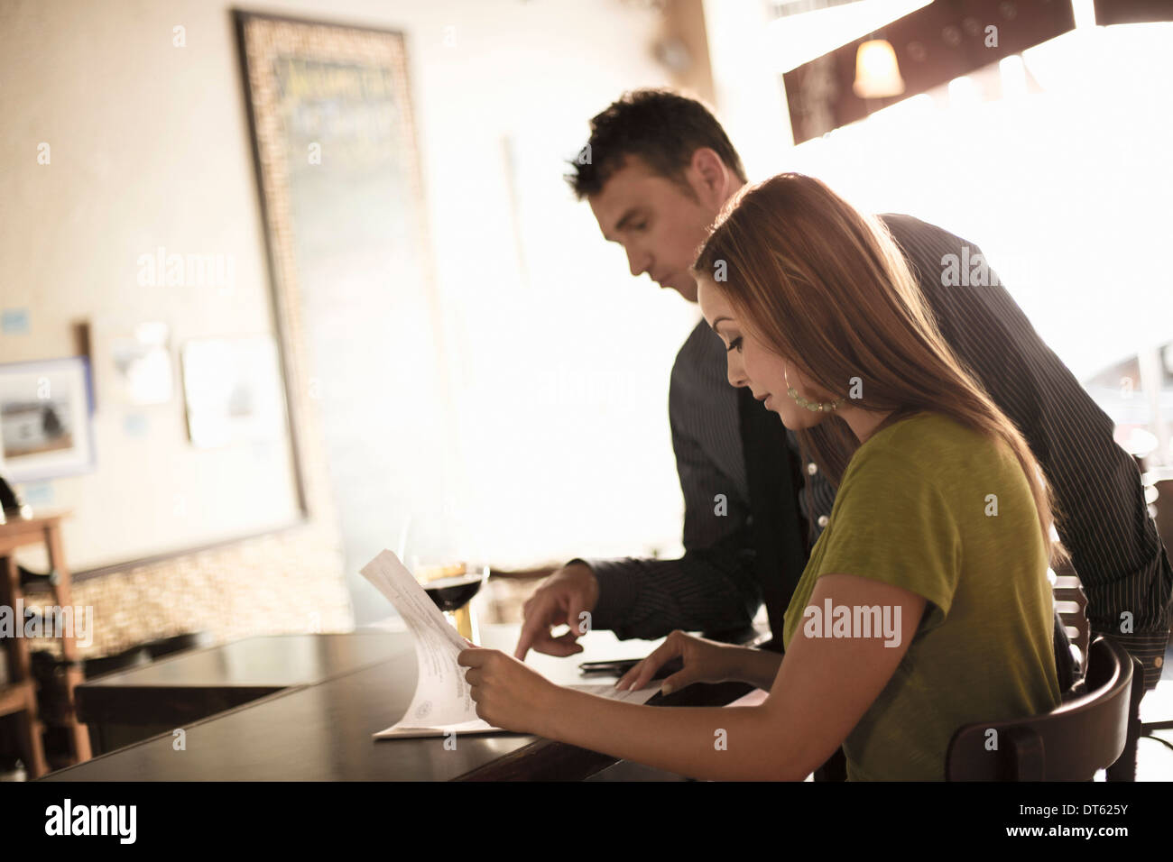 Business partners looking at paperwork in a wine bar - Stock Image
