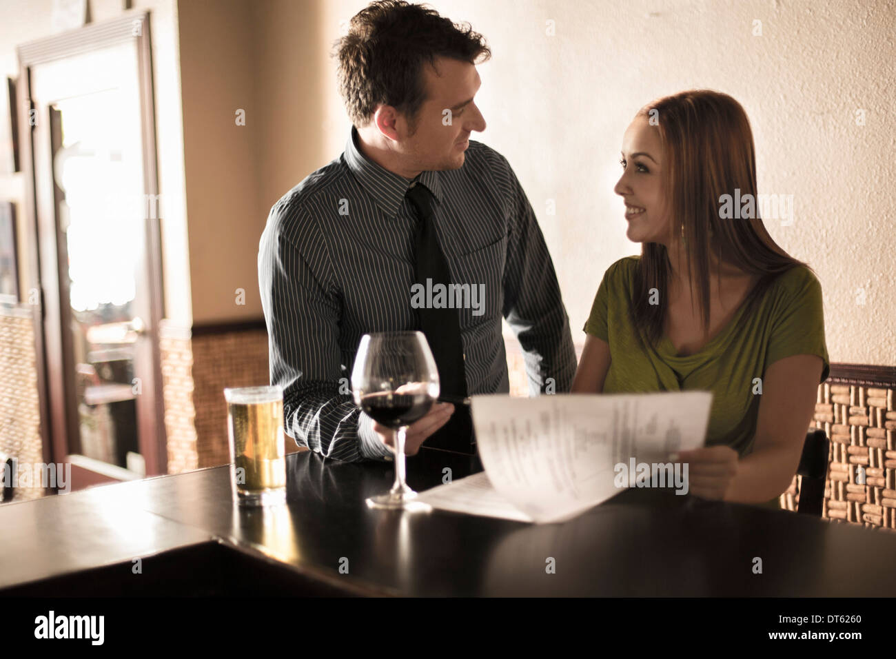 Businessman and woman looking at contract in a wine bar - Stock Image
