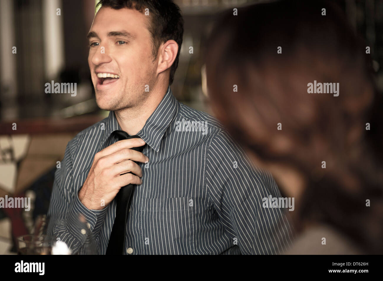 Businessman loosening tie in a wine bar - Stock Image