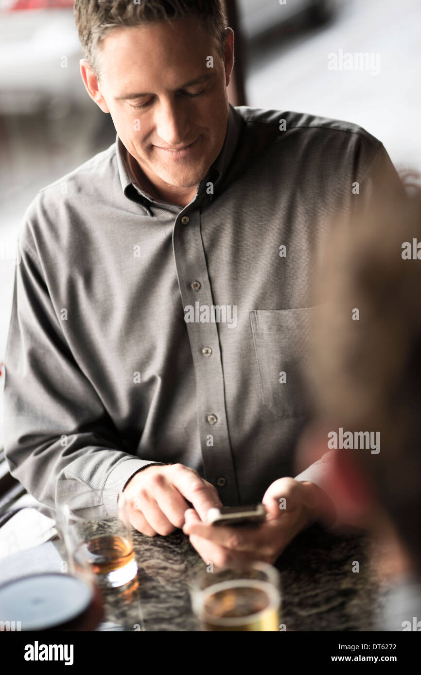Businessman using cellphone in a wine bar - Stock Image