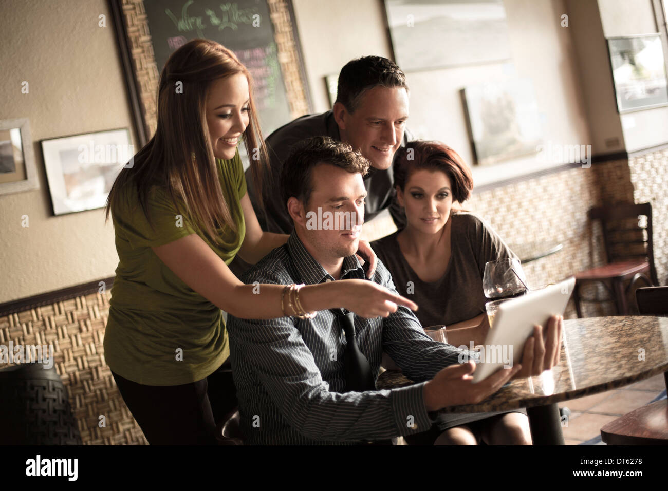 Friends looking at digital tablet in wine bar - Stock Image