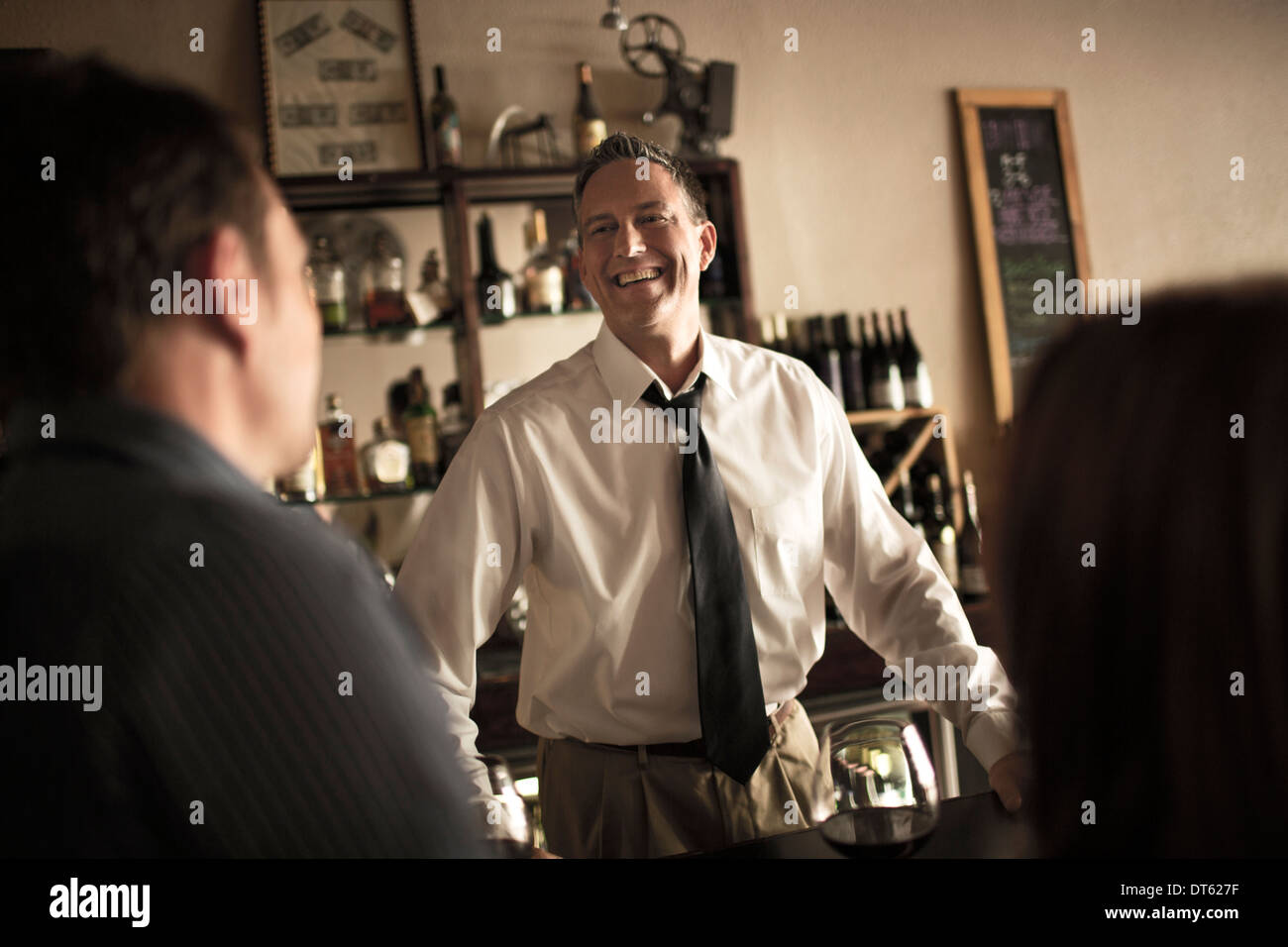 Bartender chatting with customers in wine bar - Stock Image