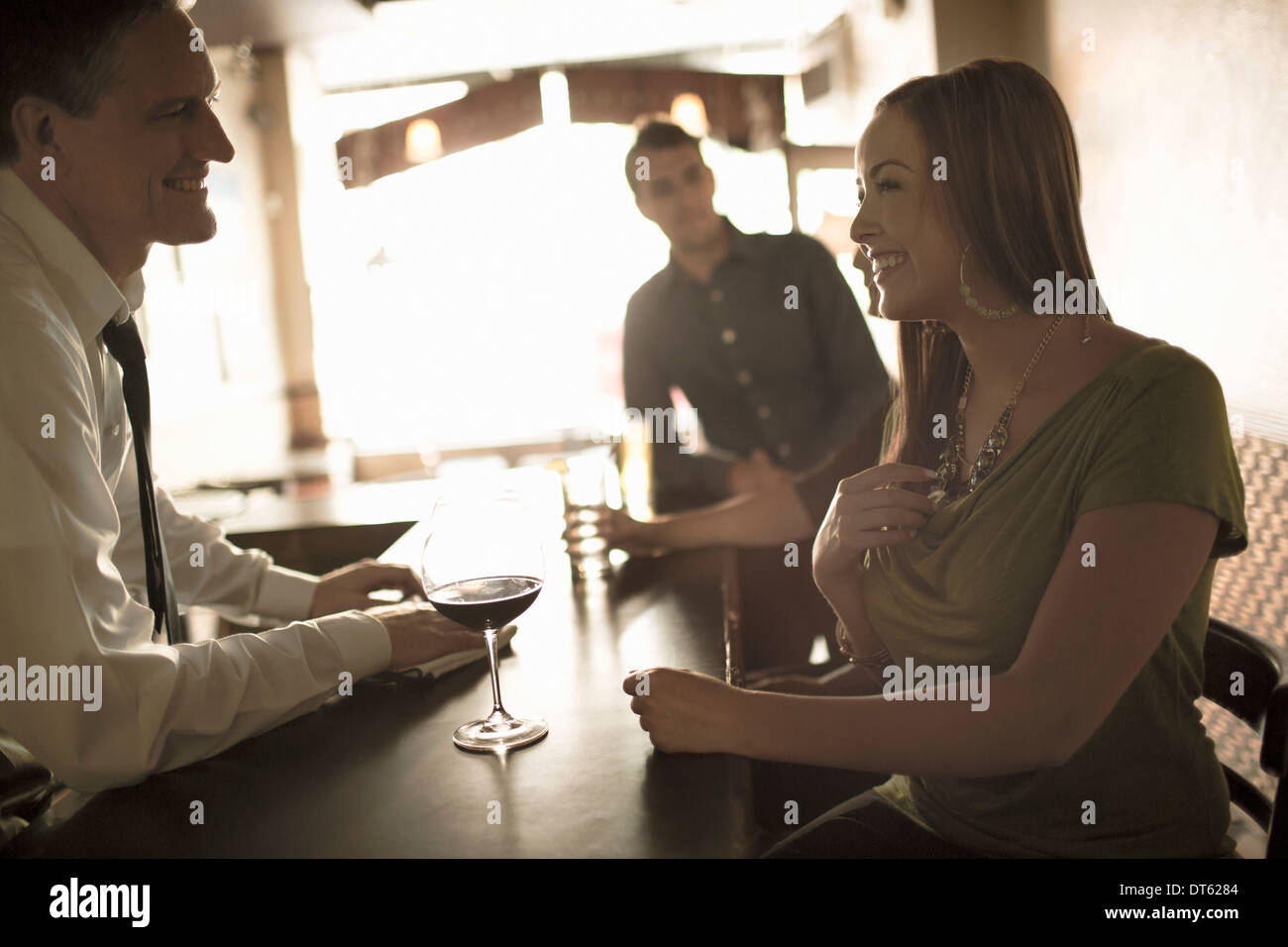 Bartender flirting with young woman in wine bar - Stock Image