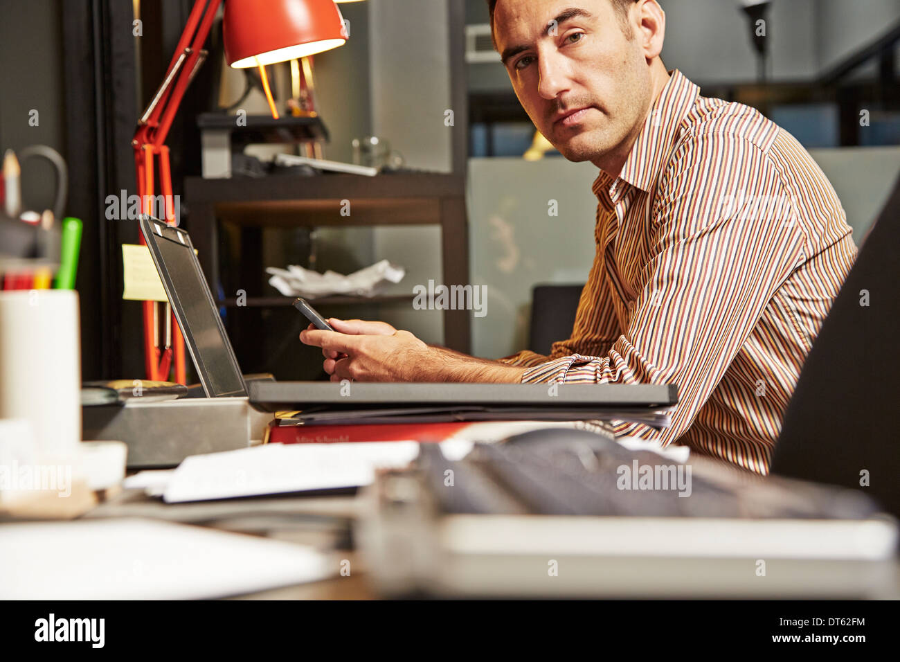 Businessman at desk using cell phone - Stock Image