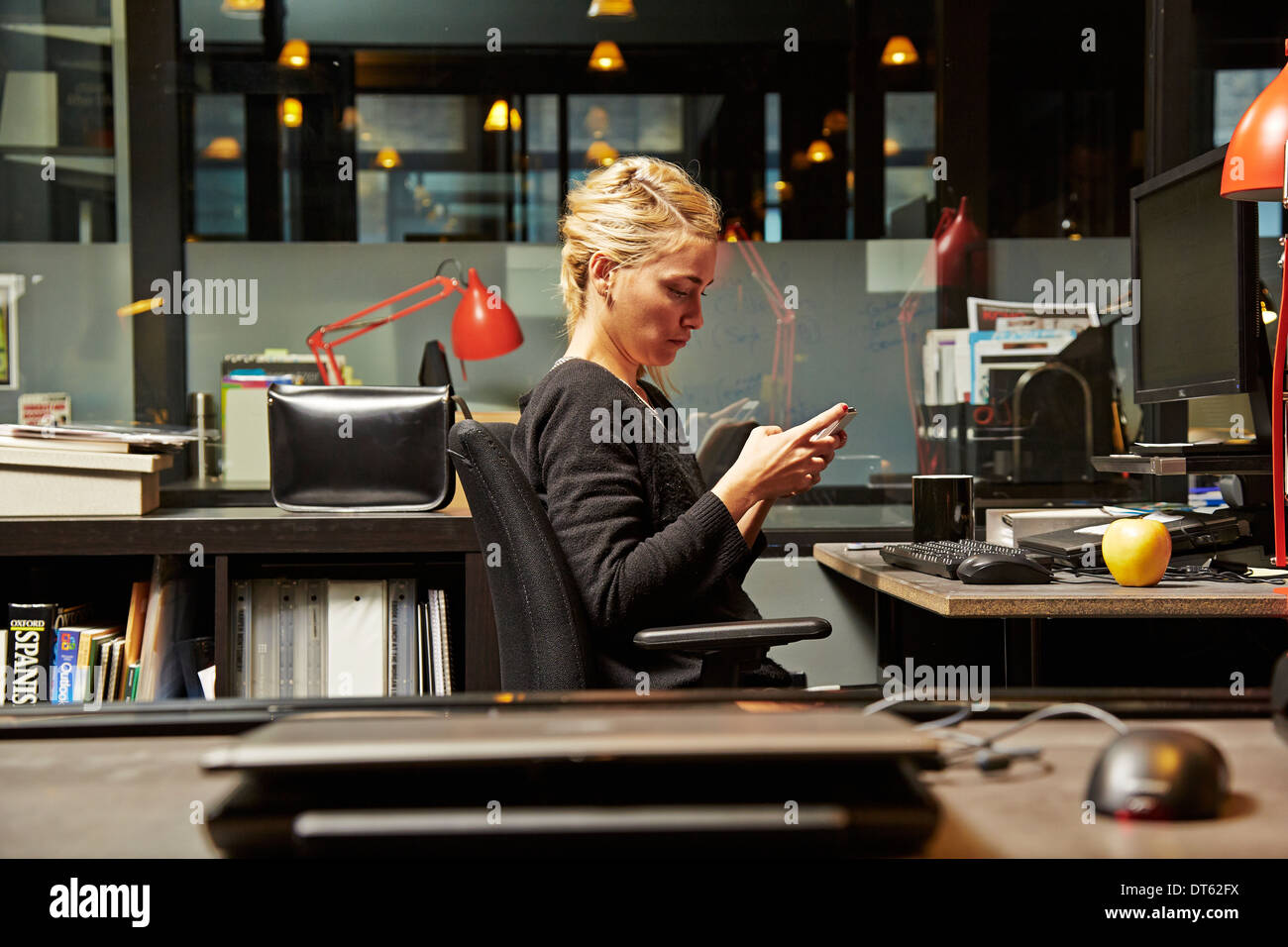 Female office worker at desk using cell phone - Stock Image