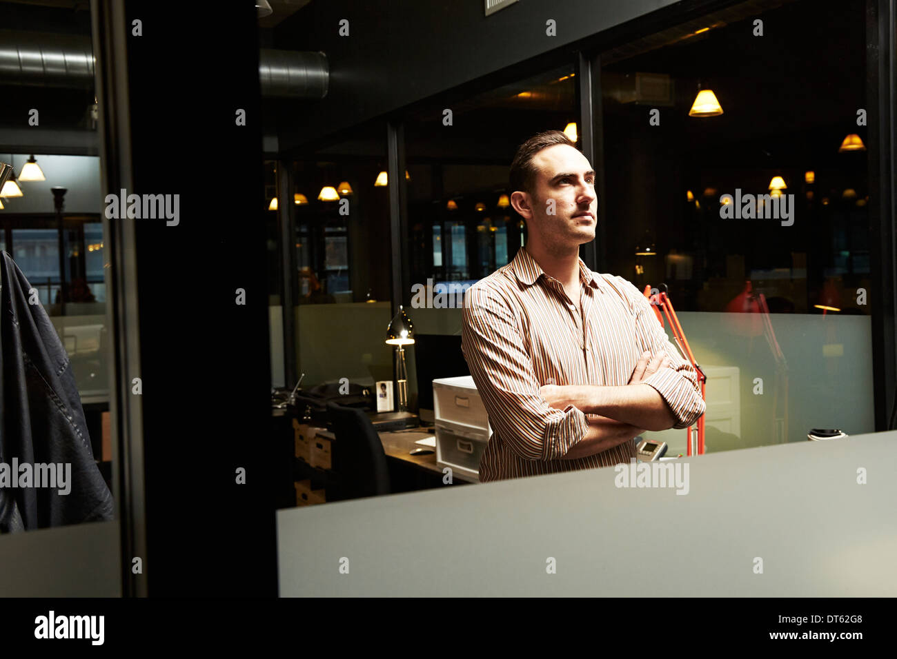 Portrait of businessman with arms folded looking away - Stock Image