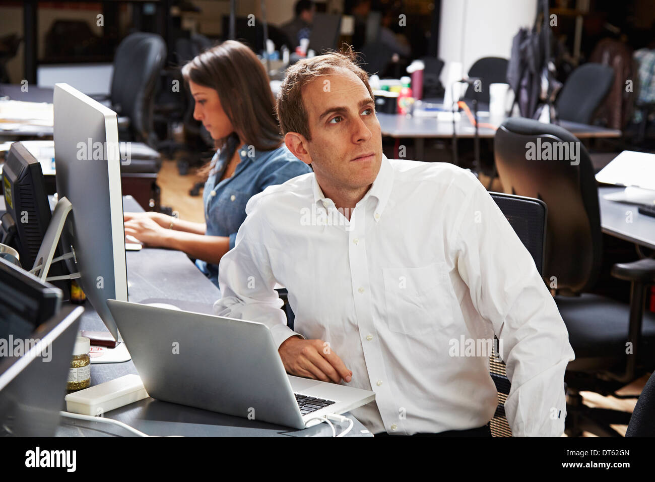 Mid adult man using laptop in office - Stock Image