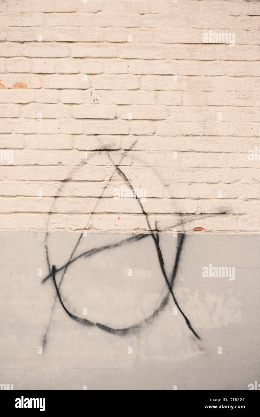 Grafitti with anarchy symbol painted on white brick wall - Stock Image