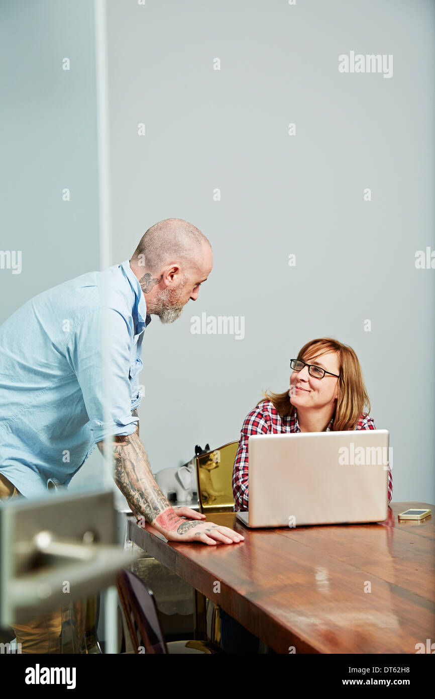 Office colleagues using laptop - Stock Image