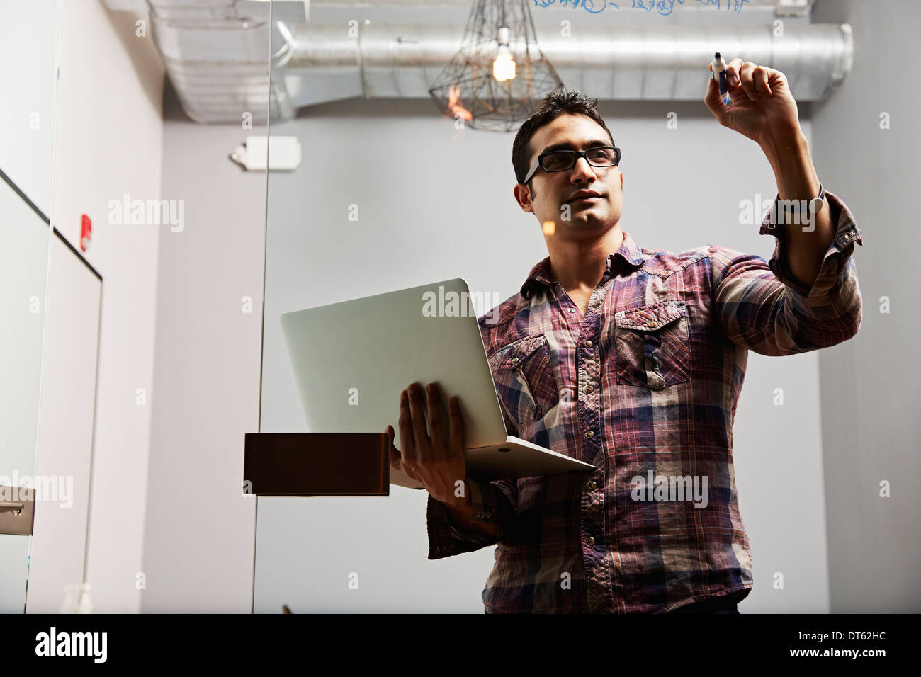 Young man holding laptop writing on glass - Stock Image