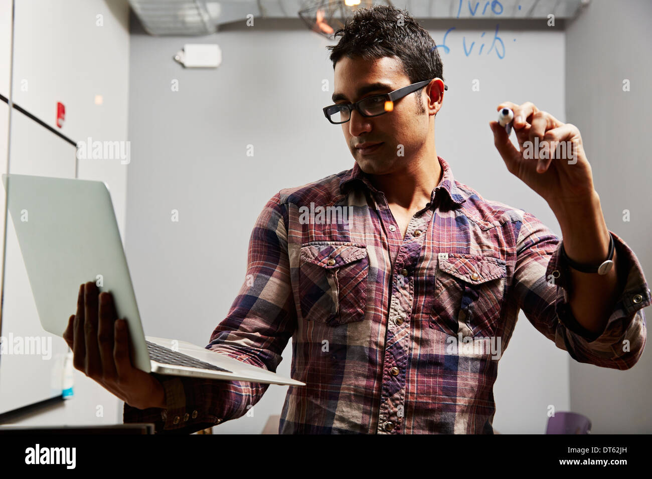 Man looking at laptop with pen in hand - Stock Image