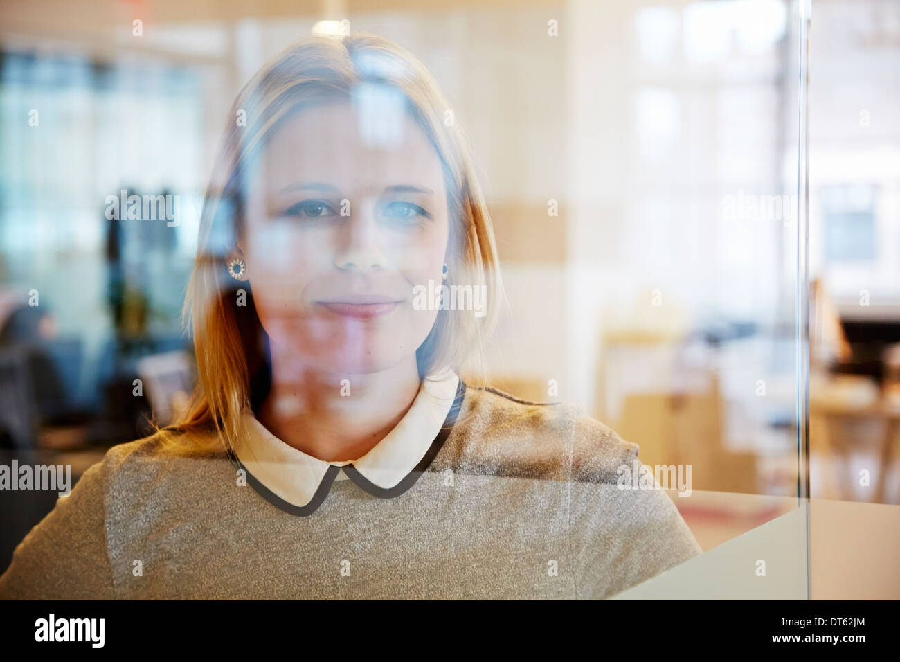 View through glass of female office worker Stock Photo
