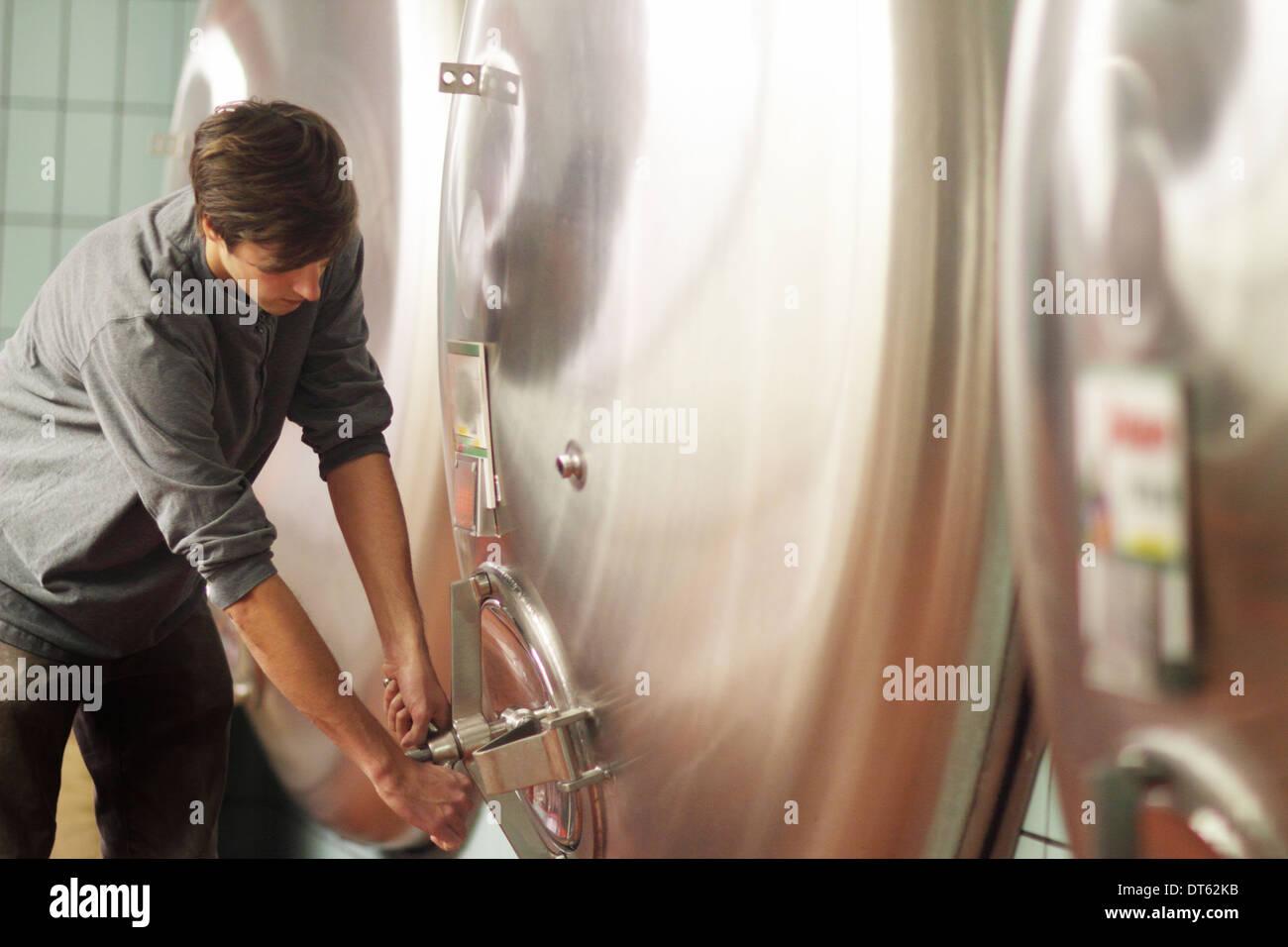 Man closing door on vat in brewery - Stock Image