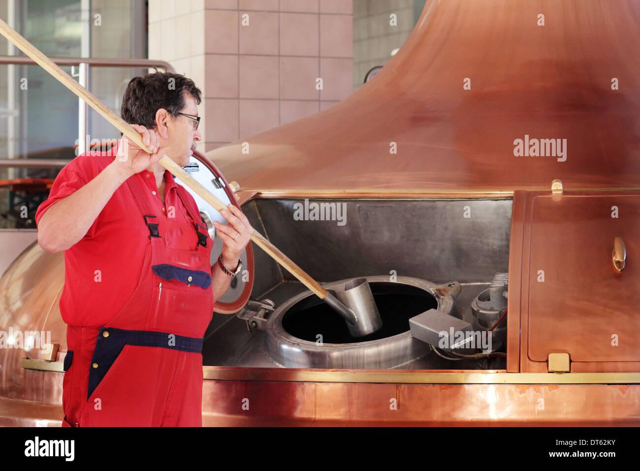 Man stirring vat in brewery - Stock Image