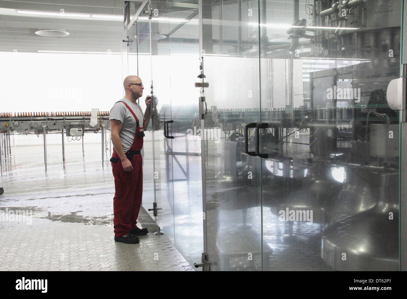 Man checking equipment in brewery - Stock Image