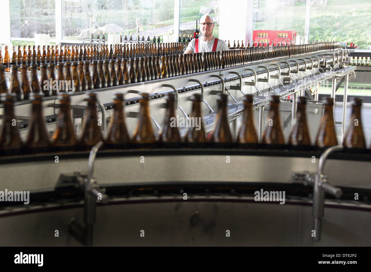Beer bottles on production line in brewery - Stock Image