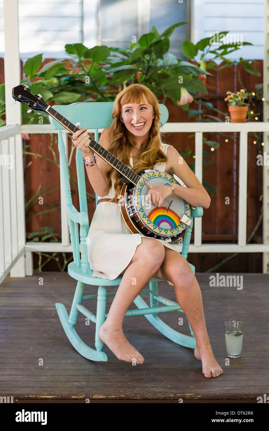Young woman sitting on rocking chair playing banjo - Stock Image
