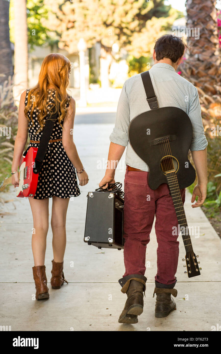 Young couple walking along street carrying guitars and amplifier - Stock Image