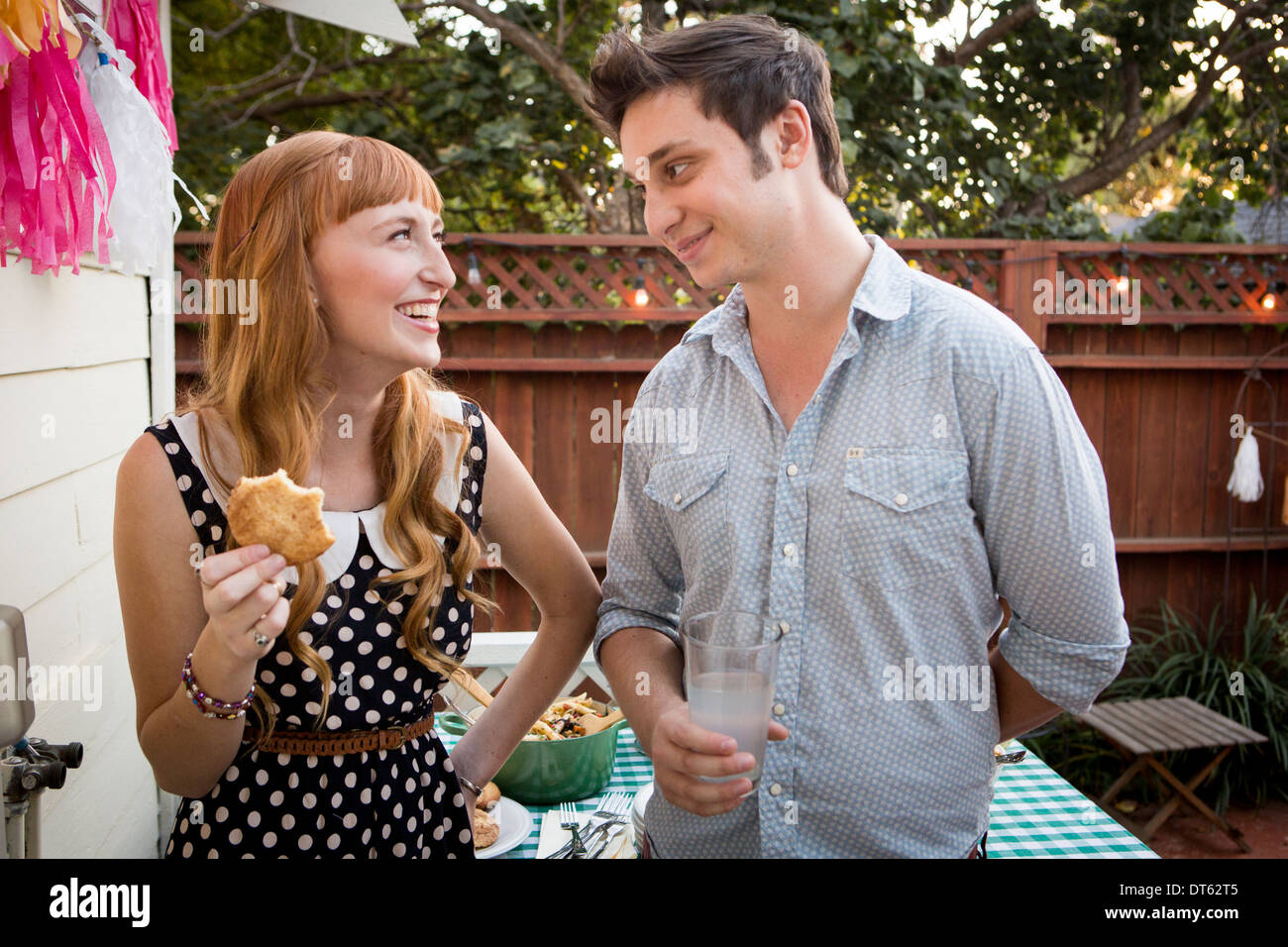 Young couple enjoying picnic lunch in garden - Stock Image