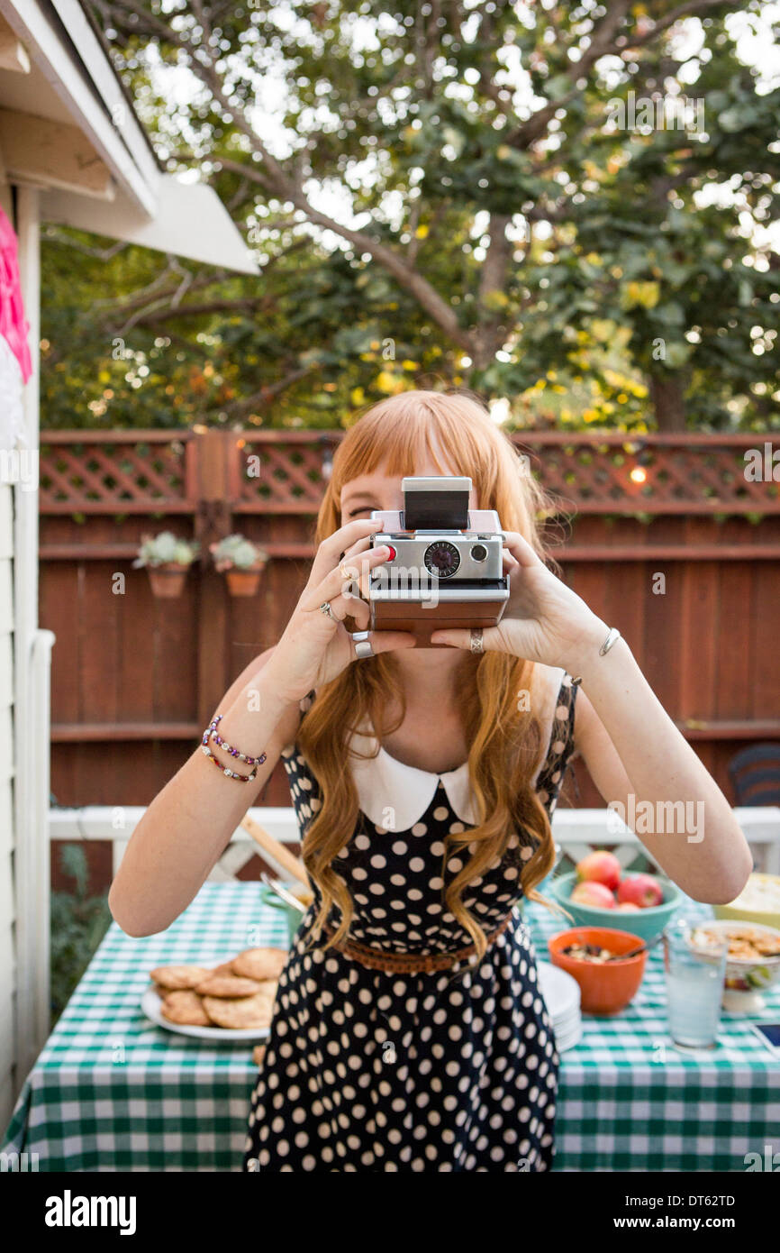 Young woman photographing with polaroid camera - Stock Image