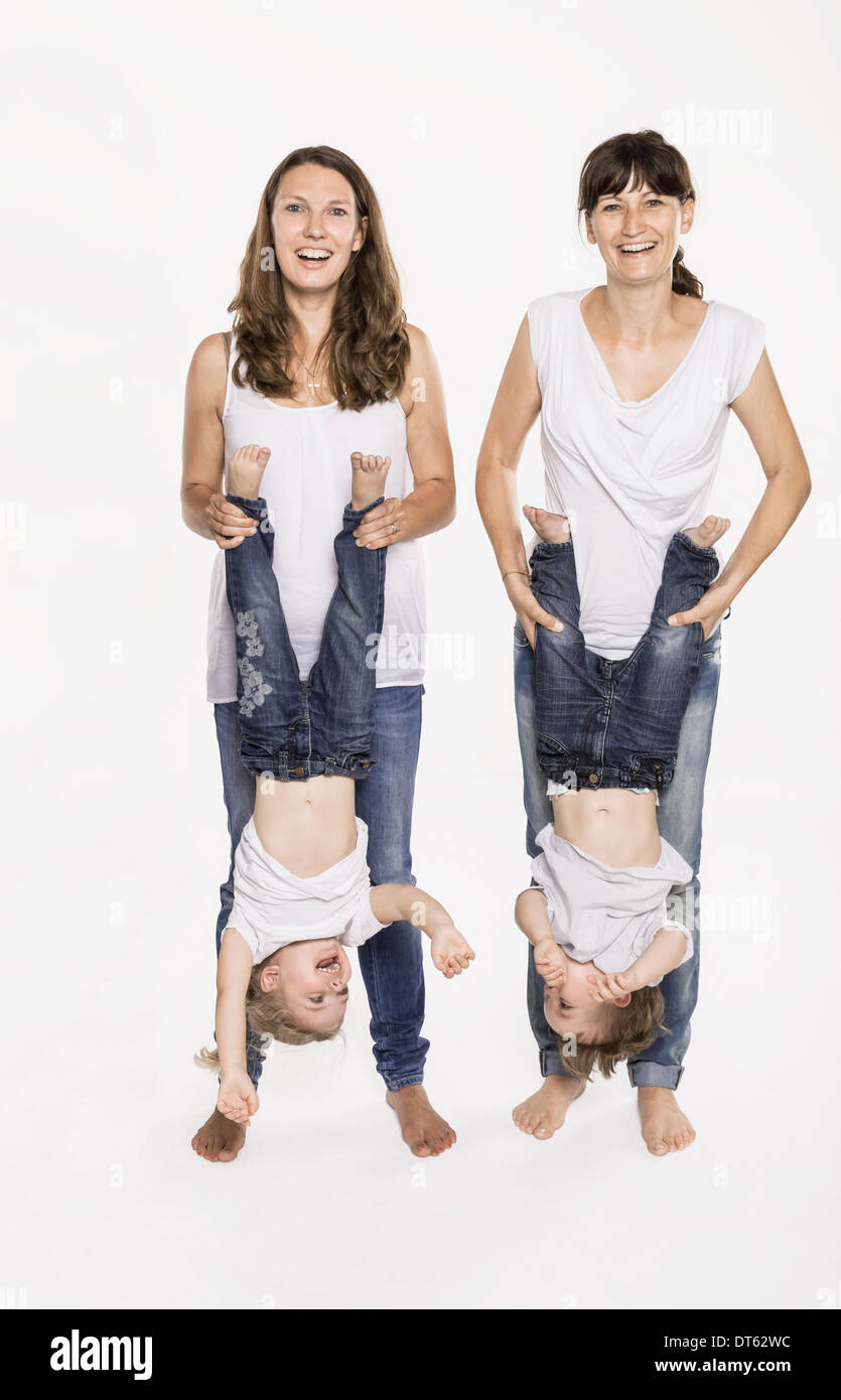 Studio portrait of two mid adult mothers holding their children upside down - Stock Image