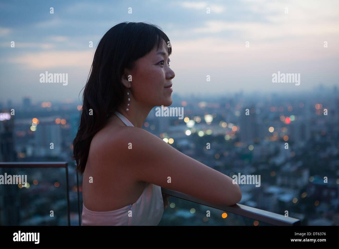Woman on balcony, Bangkok, Thailand - Stock Image