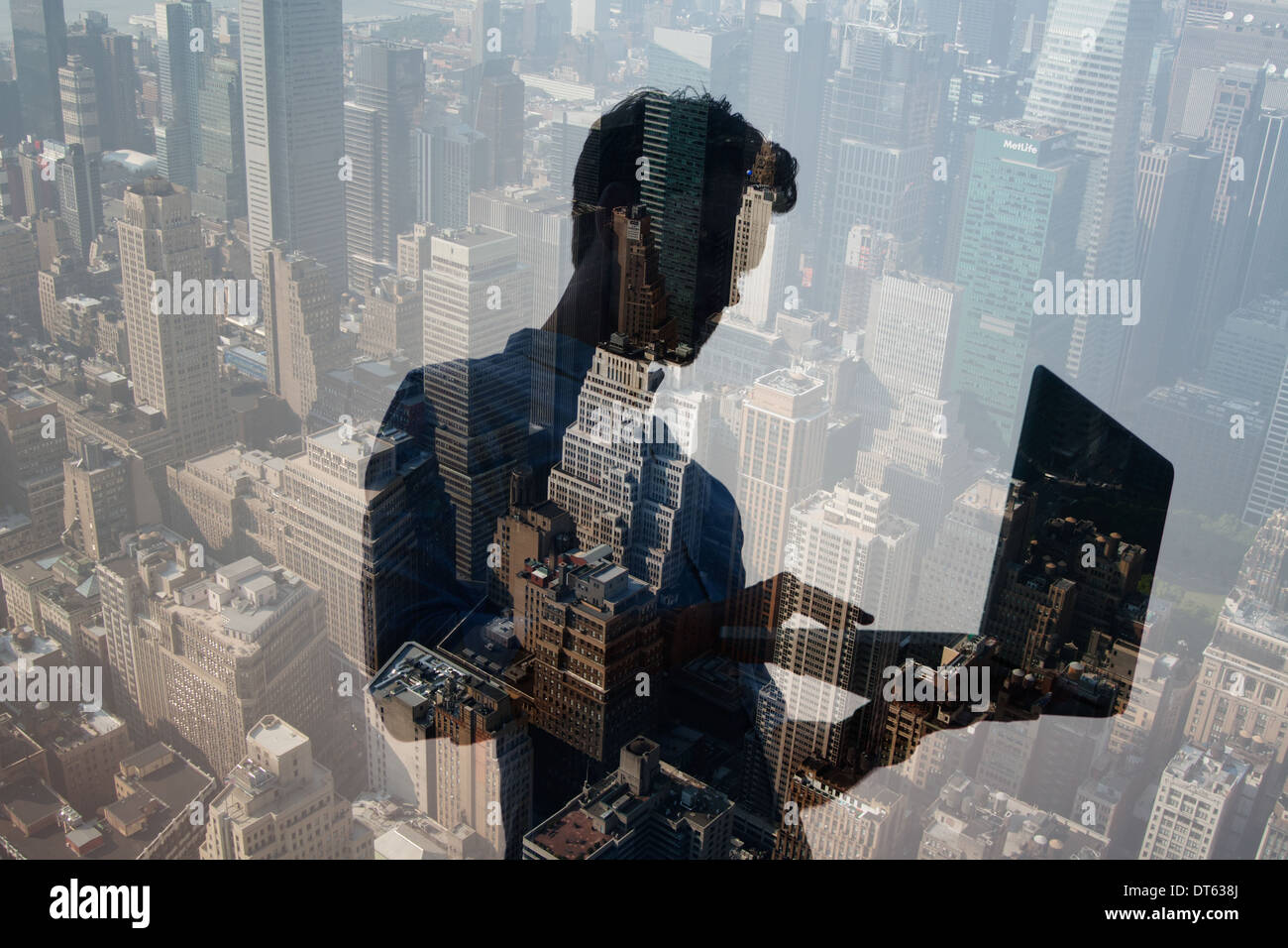 Man using laptop against cityscape, New York, USA - Stock Image
