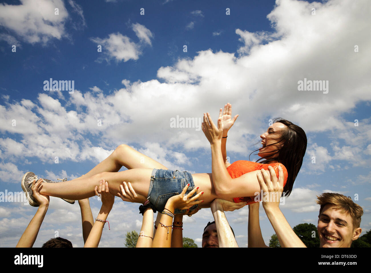 Cropped shot of friends hands holding up young woman - Stock Image