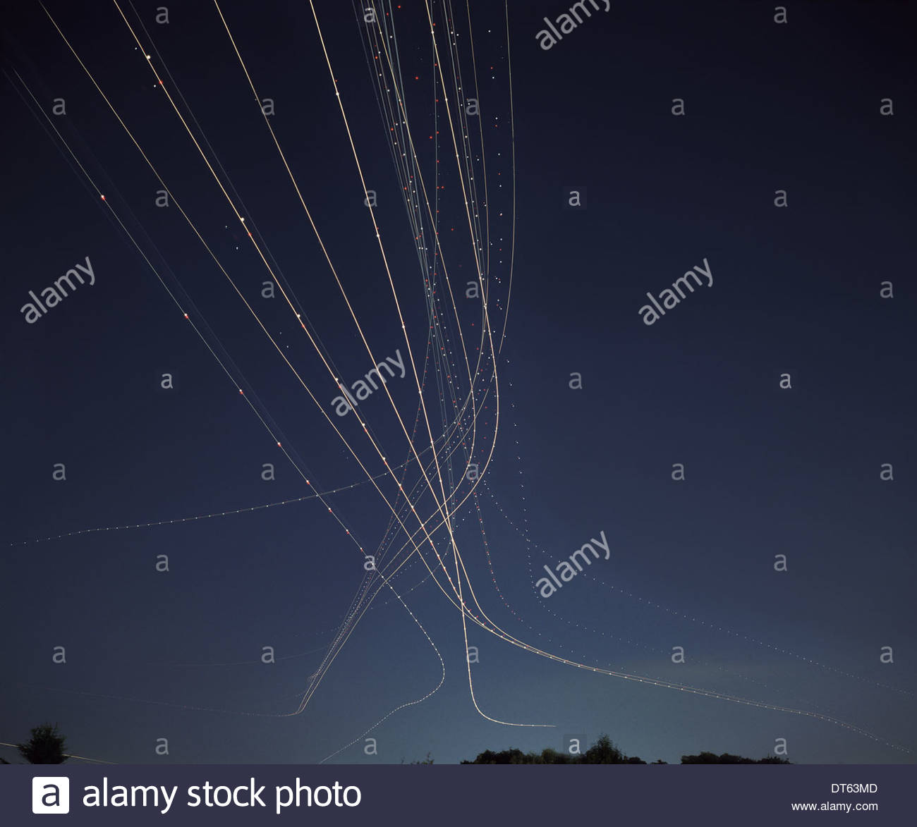 Light trails from aircraft taking off in night sky Stock Photo