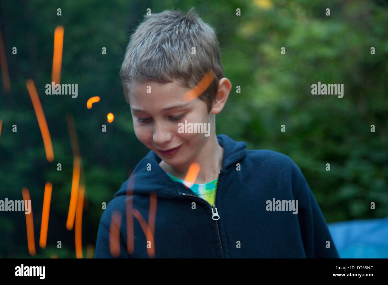 Boy with sparks from campfire - Stock Image