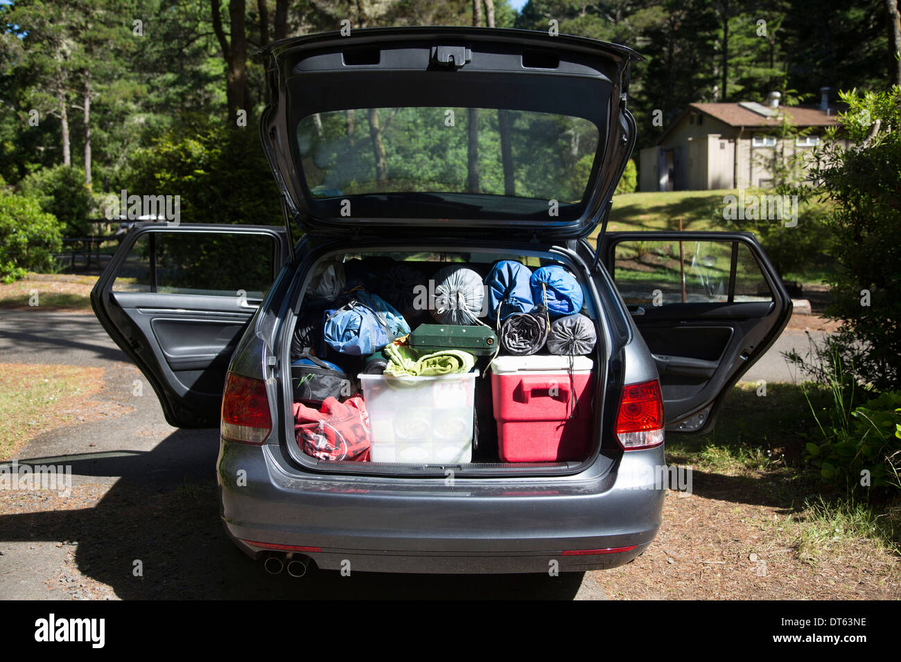 Car boot packed full with camping equipment - Stock Image