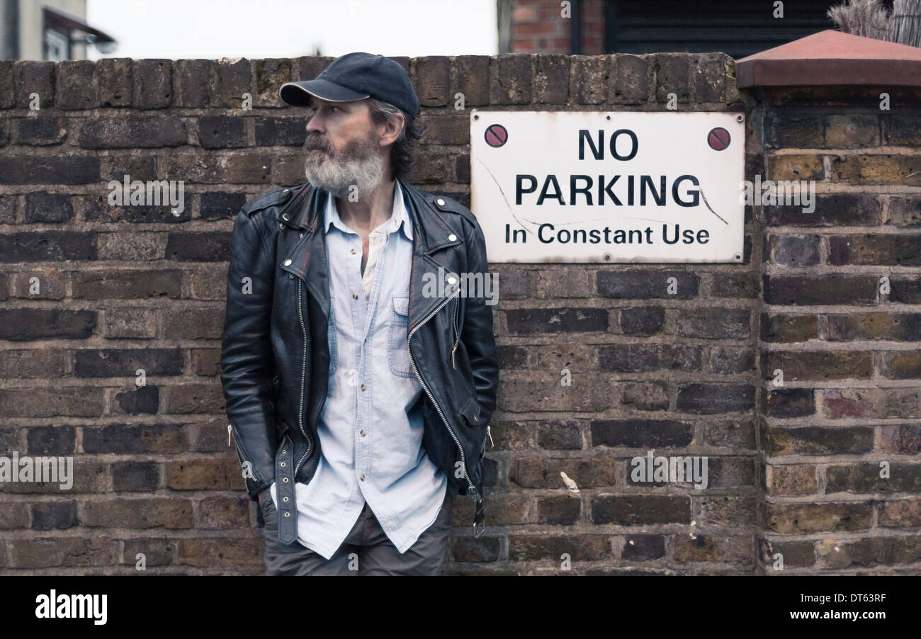 Mature man by no parking sign on brick wall - Stock Image