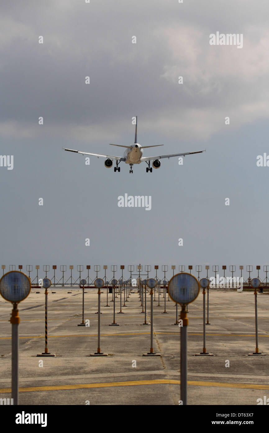 Commercial air transport flight. Airplane overflying airport runway approach lights moments before landing - Stock Image