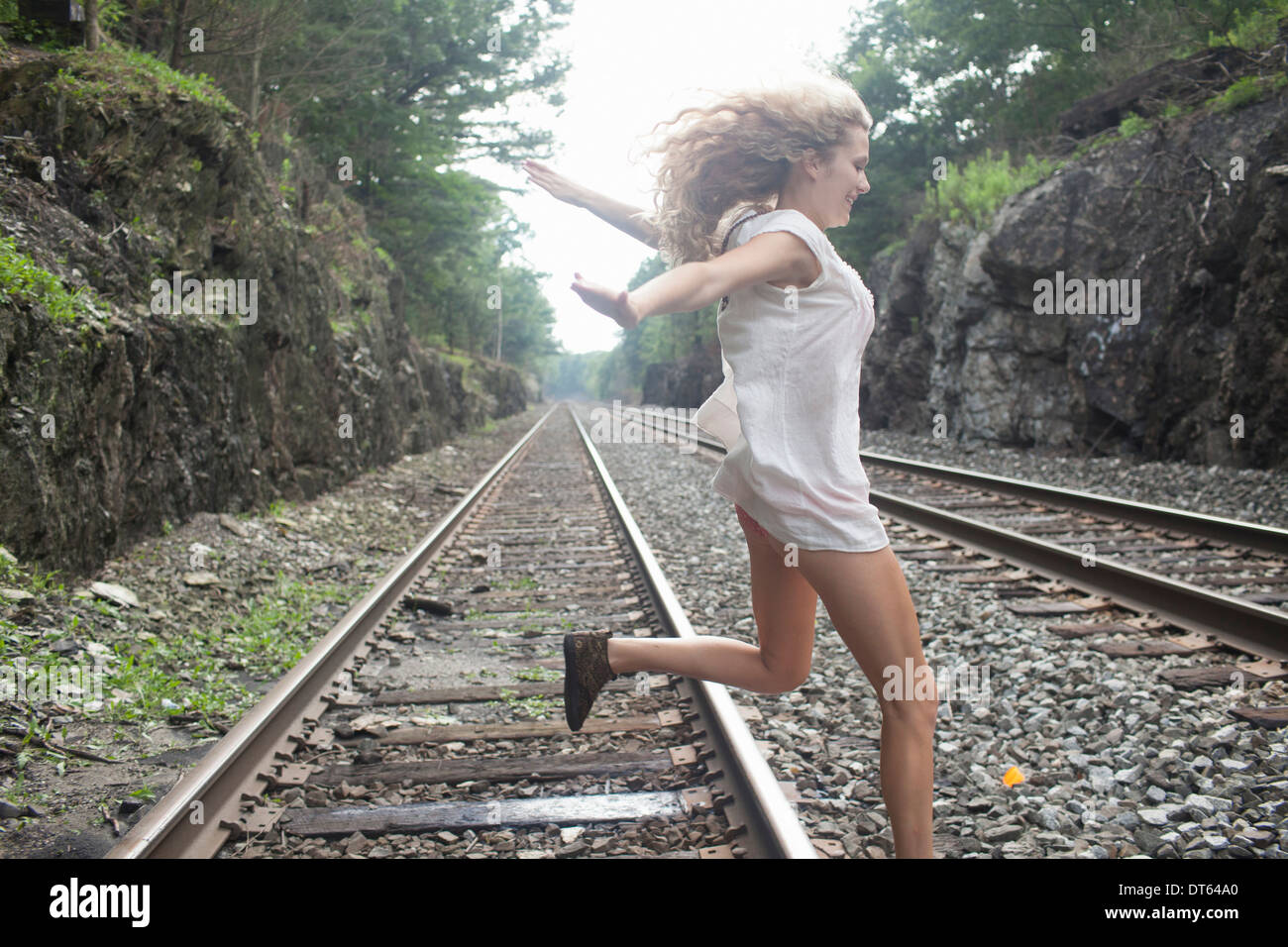 Teenage girl jumping over railway track - Stock Image