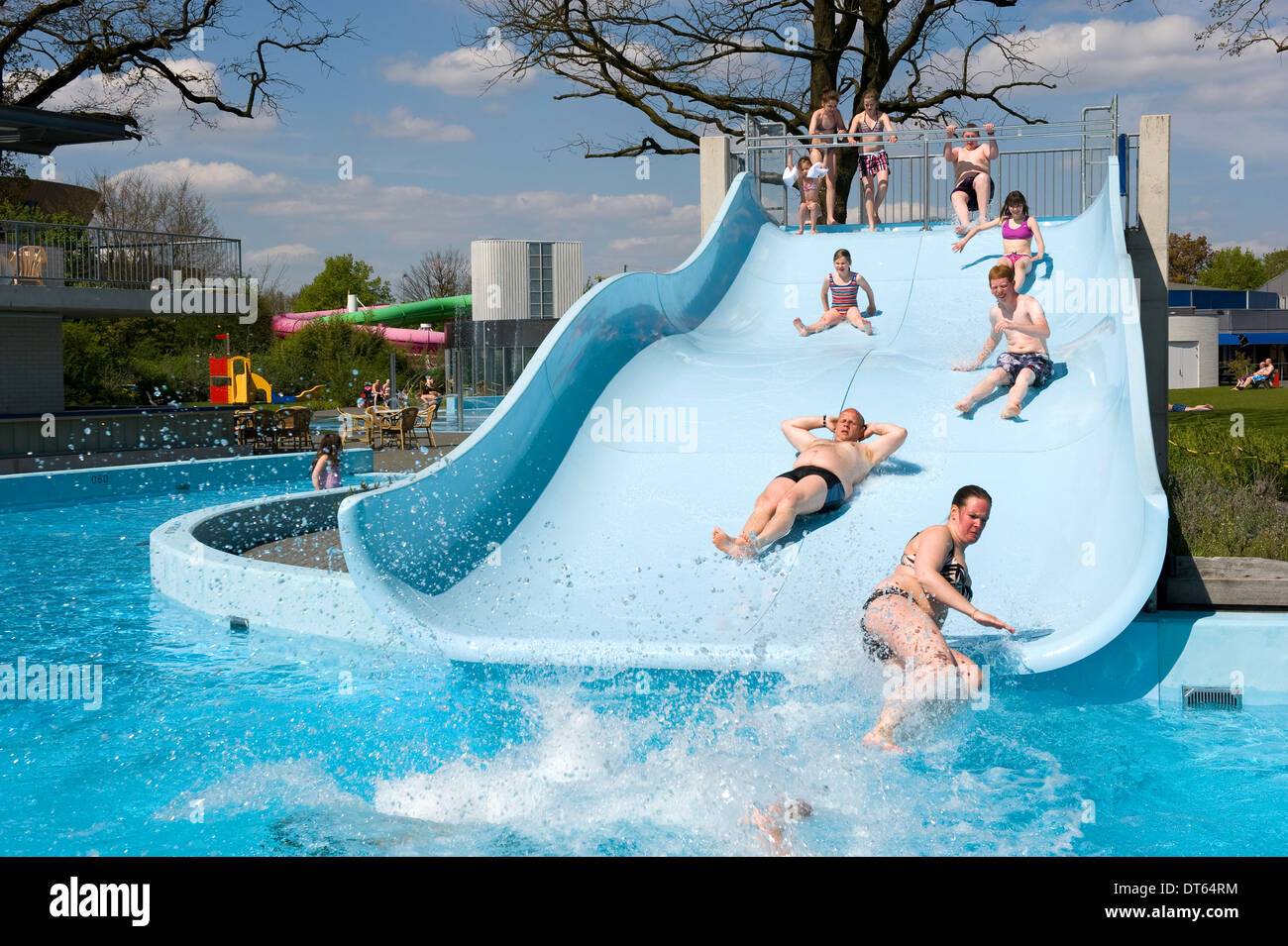People are sliding on a water slide of a public pool - Stock Image