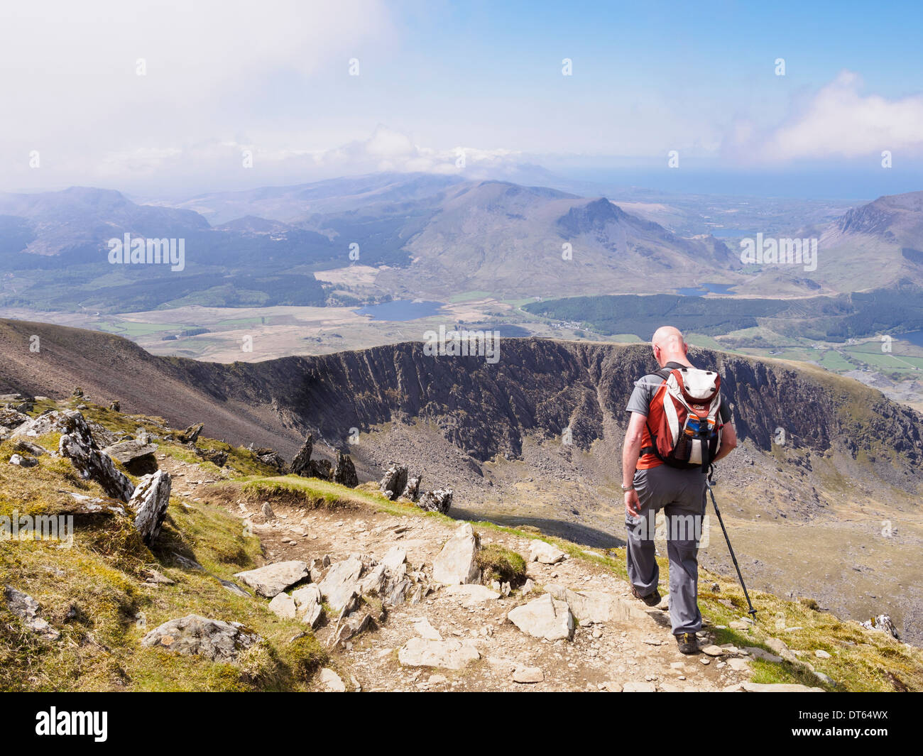 Hiker carrying a rucksack walking down Rhyd Ddu path on Bwlch Main with view south to Llechog from Mt Snowdon mountain Stock Photo