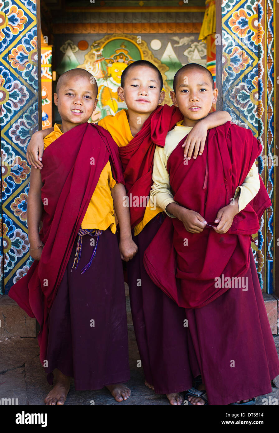 Bhutan, South Asia, Punakha, Three young novice boy monks standing in doorway of Chimi Lakhang temple in the old capital. - Stock Image